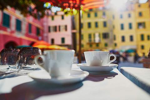 dwie filiżanki kawy, w tle włoskie miasteczko